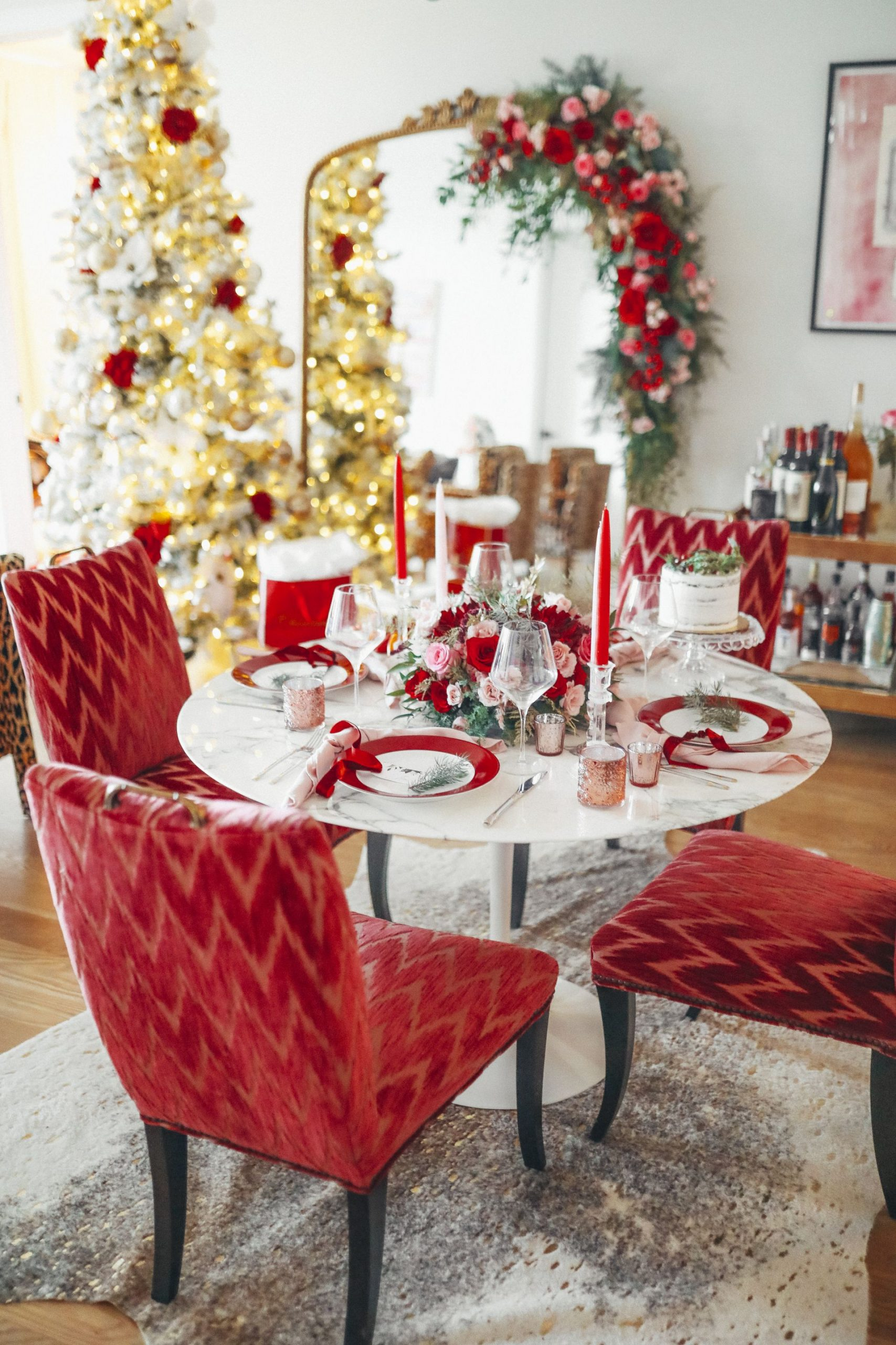 chicago event planner, chicago home, anthropologie primrose mirror, revolve red dress, king of christmas flocked tree, floral garland on mirror, chicago florist, best chicago glam birthday, glam dining room, Crate and barrel red plates, red themed party