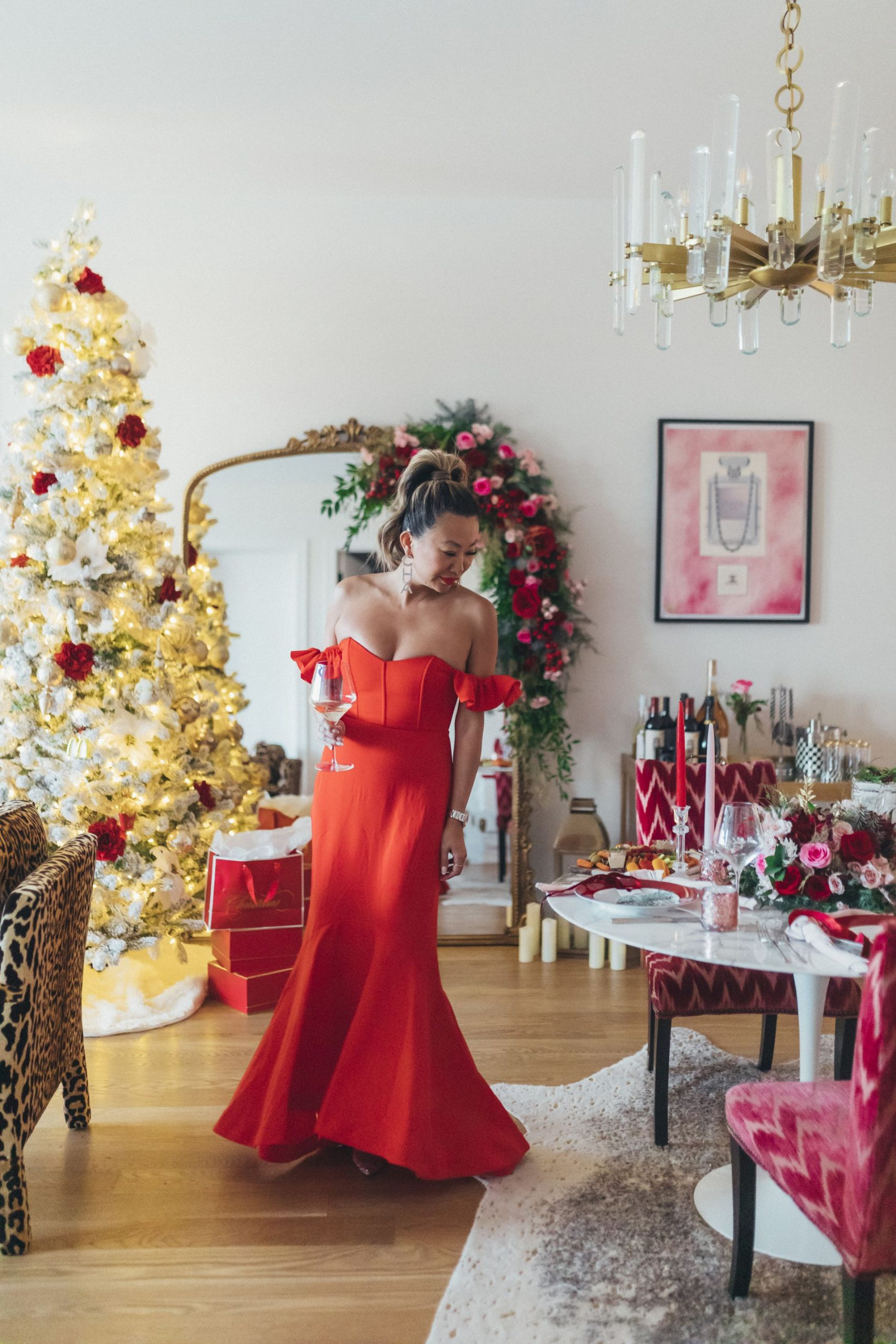 chicago event planner, chicago home, anthropologie primrose mirror, revolve red dress, king of christmas flocked tree, floral garland on mirror, chicago florist, best chicago glam birthday